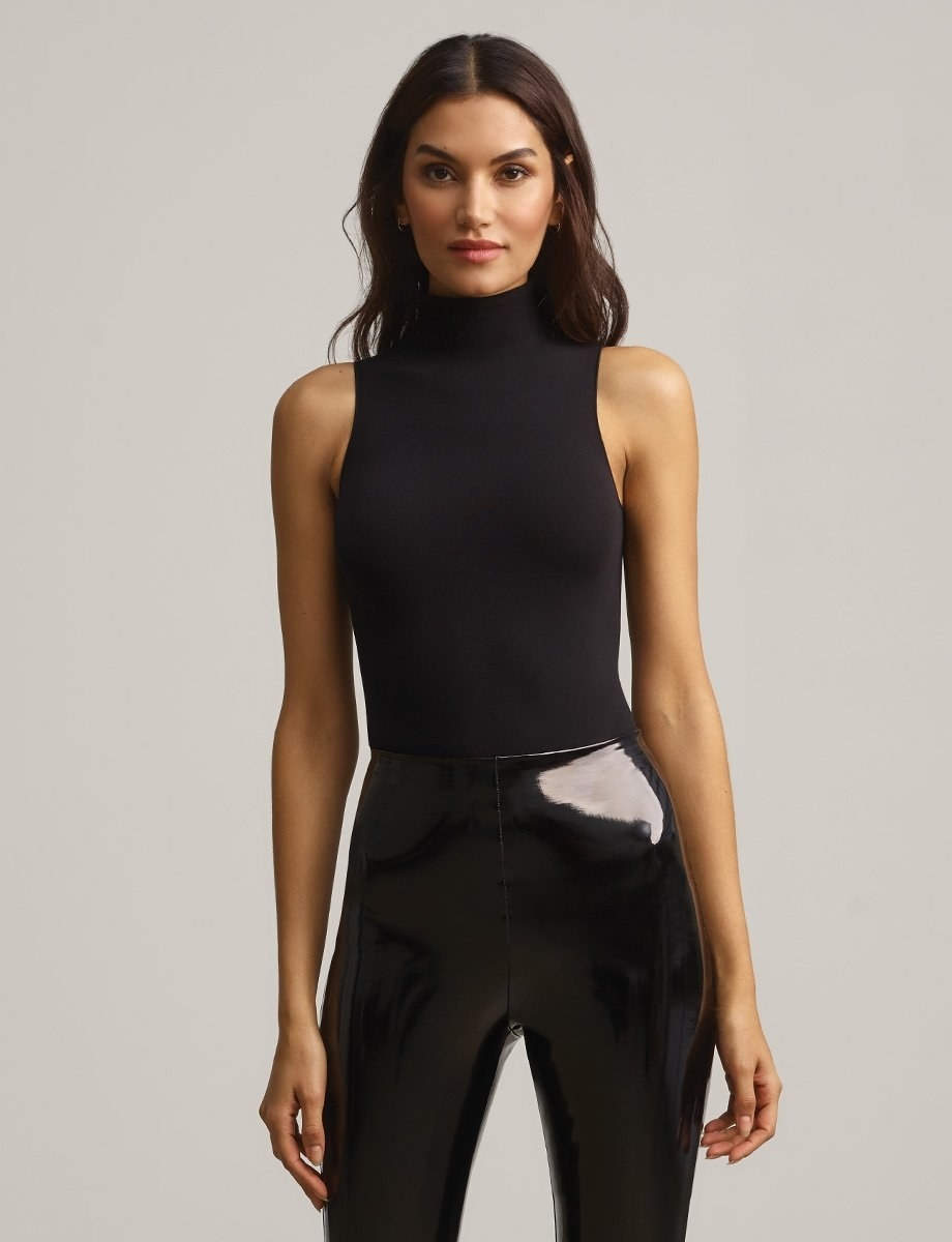 a model in a black body suit and leggings