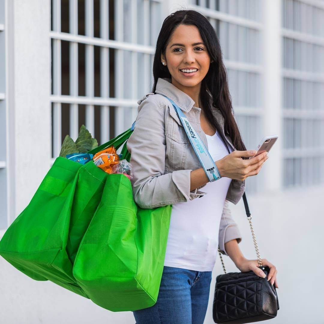 A model is holding bags of groceries using a Grocery Gripps strap around her shoulders