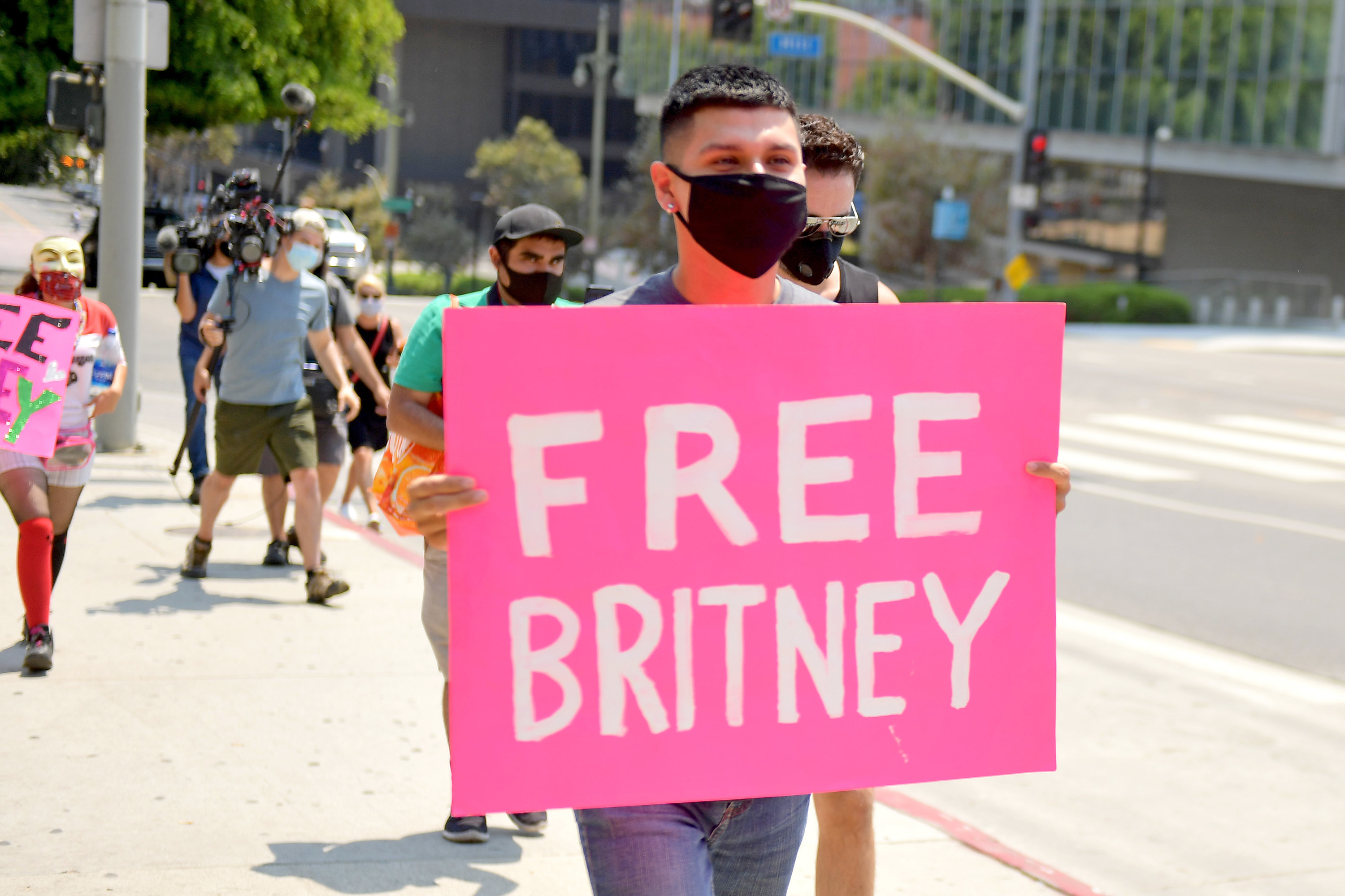 """A person walking with a """"Free Britney"""" poster"""