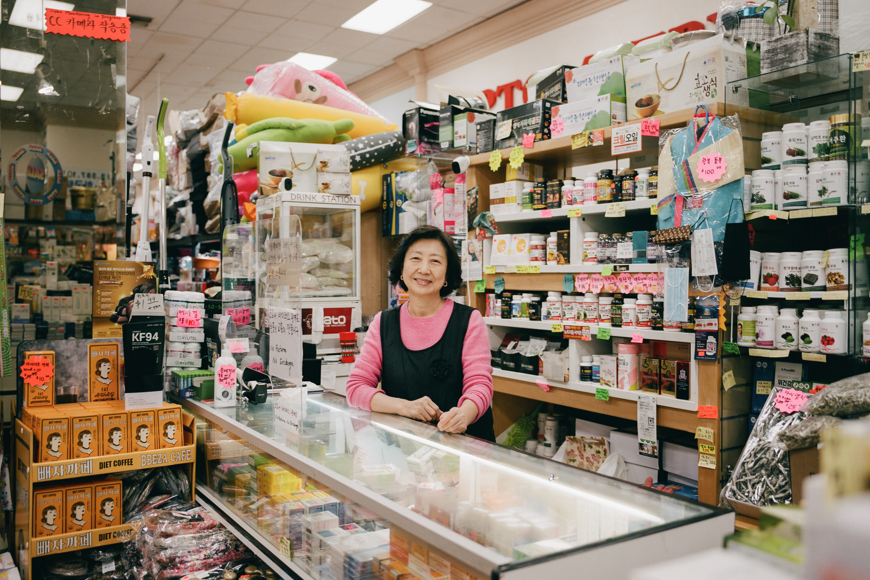 A woman smiles at the camera from behind the counter of her home goods store, the shelves behind her filled to the ceiling with merchandise