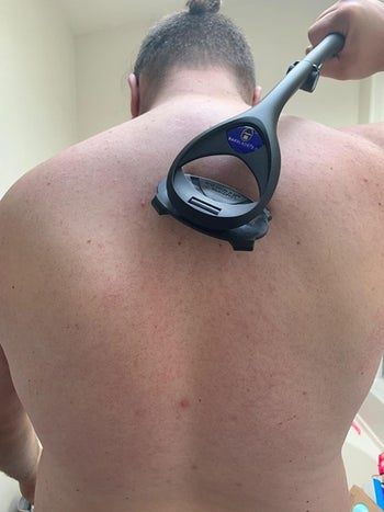 A reviewer photo of a person using the back shaver on their back