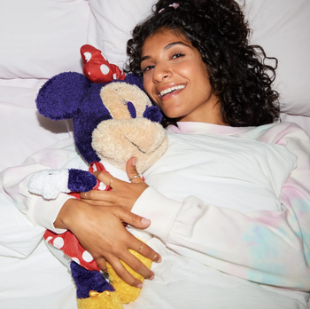 a model in bed with the minnie mouse plush doll