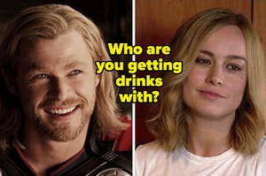 Thor looks up at someone as he smiles brightly and Carol Danvers narrows her eyes as she smiles.