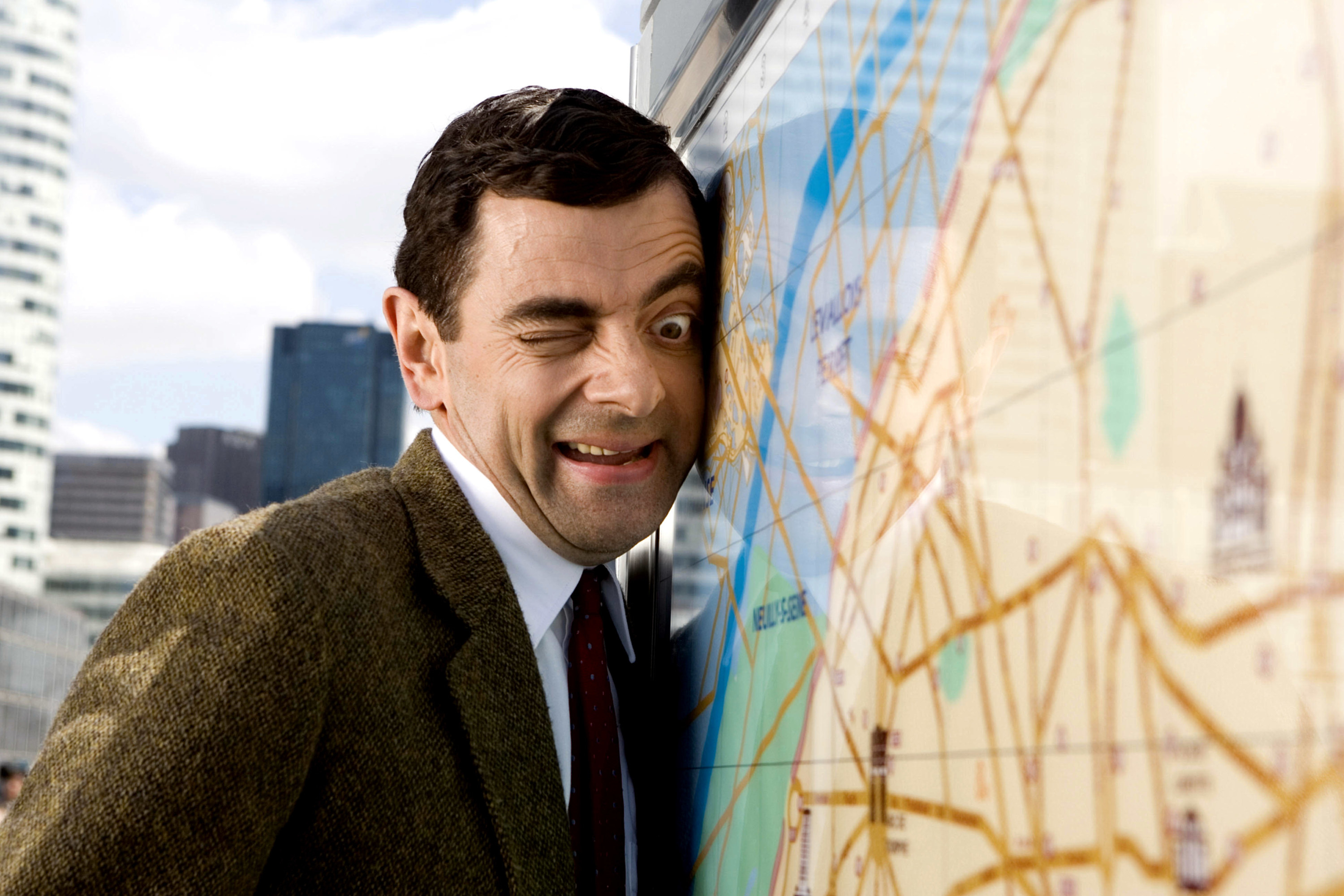 Mr. Bean with his face smushed against a map