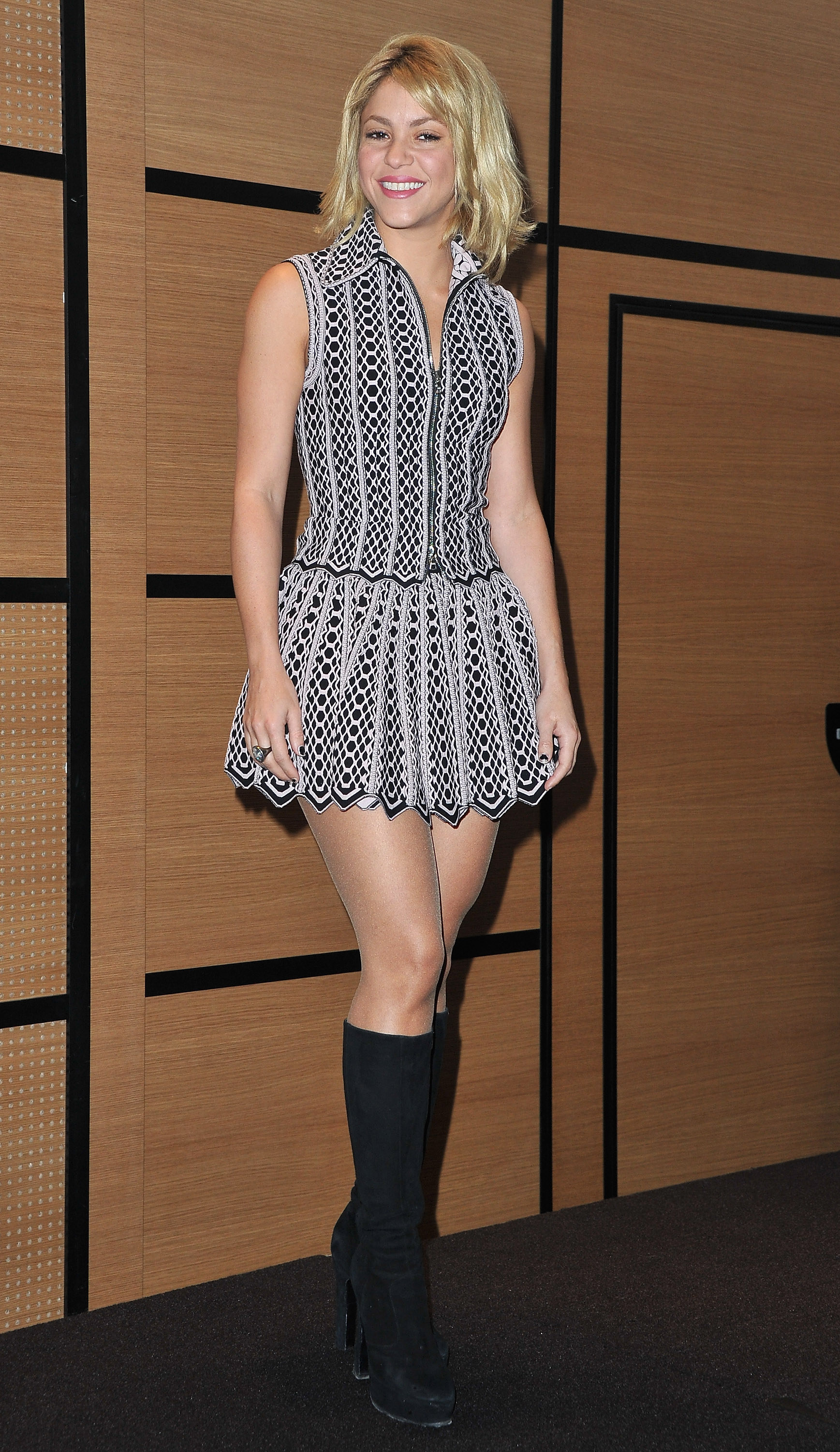 Shakira shows off the rest of the outfit, a sleeveless black and white form-fitted mini dress that flares at the bottom