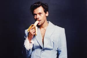 One Direction's Harry Styles eats a banana while dressed in a pastel blue suit.