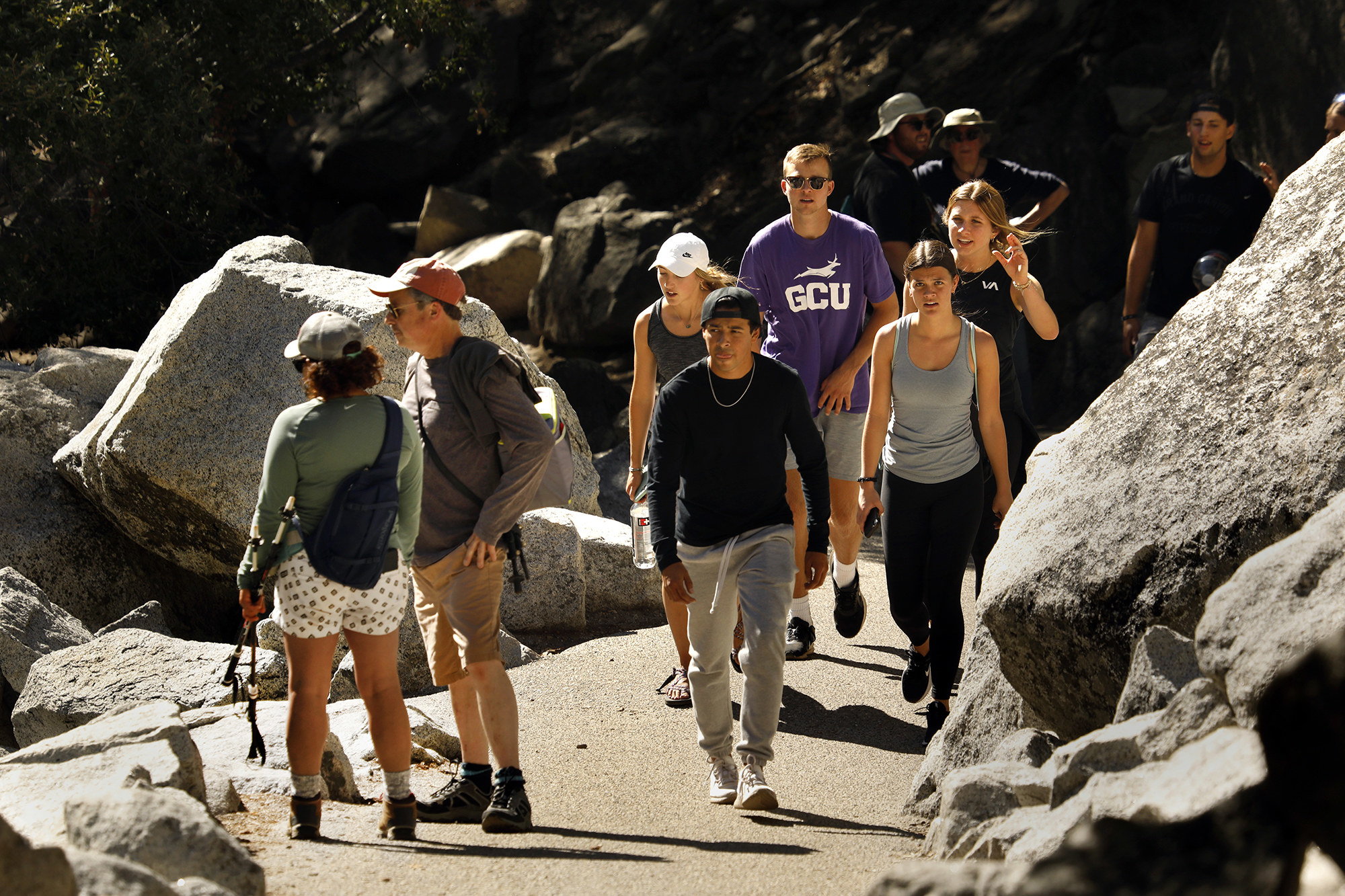 Groups of people, most unmasked, walking up a hiking trail in Yosemite National Park