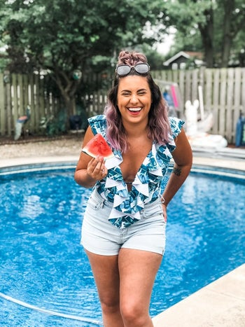 reviewer wearing the v-neck ruffle one-piece in blue and white pattern