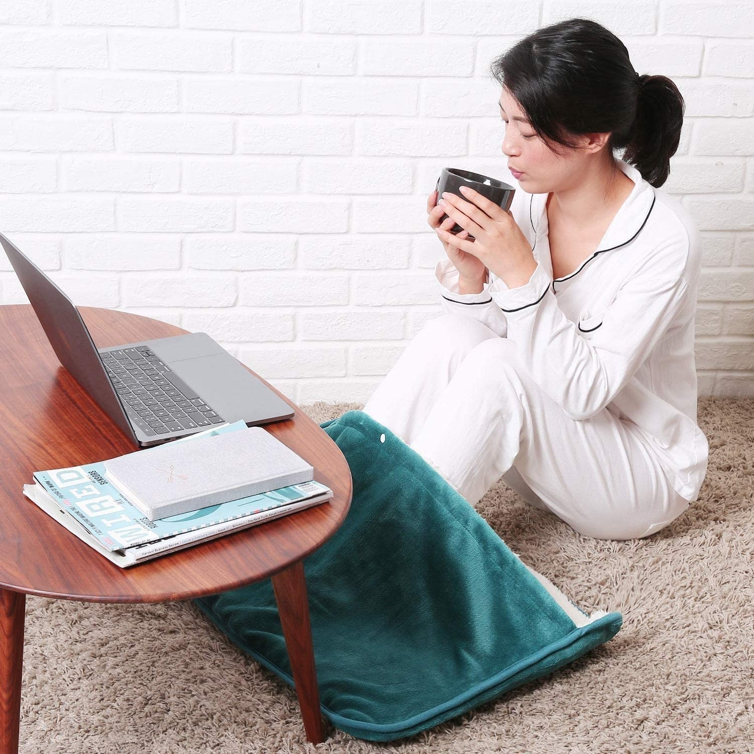 A person sitting at a coffee table with their feet tucked into the oversized warming mat