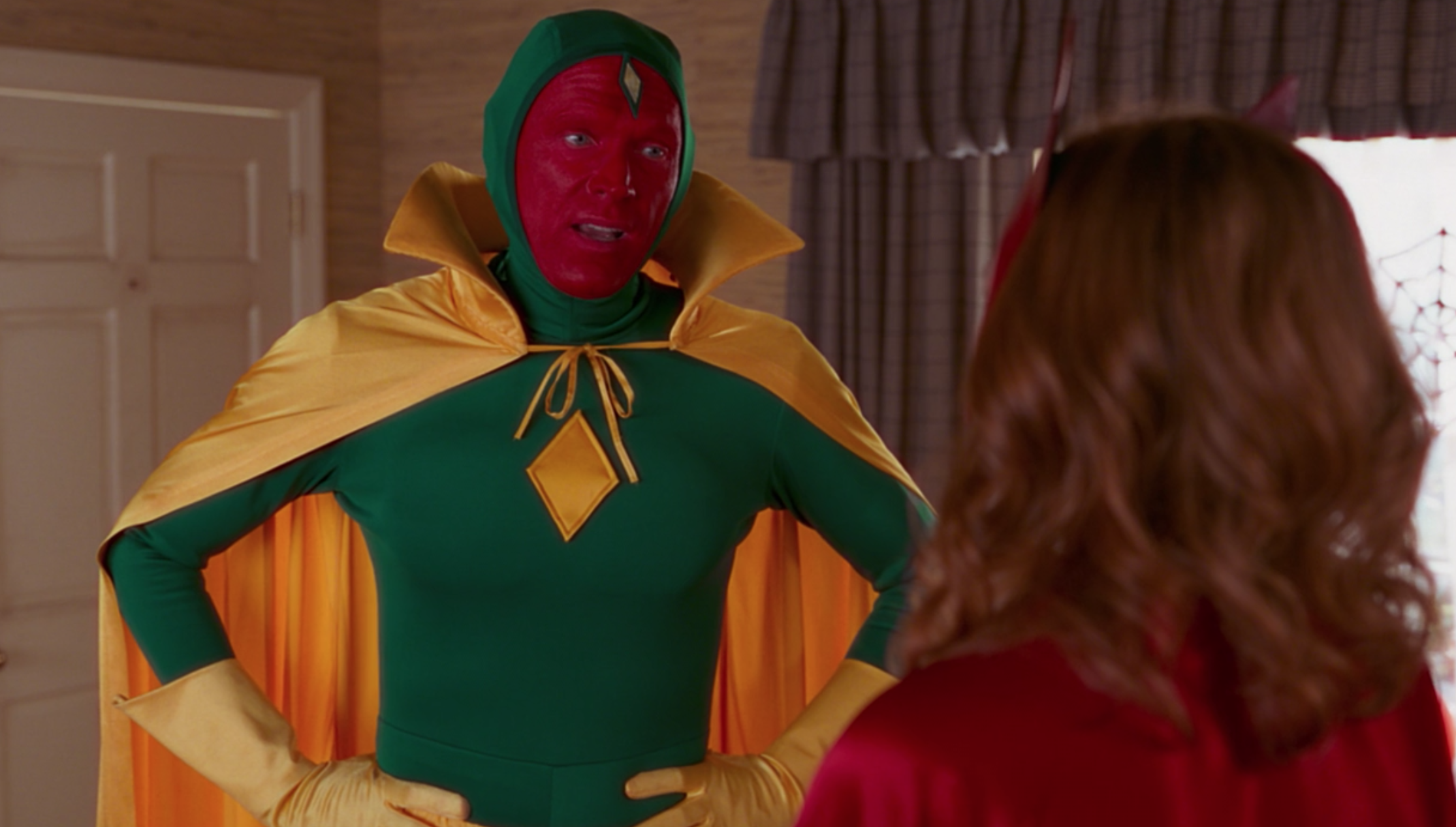 Vision wears a green body suit, a yellow cape, and matching gloves with his entire face painted bright red.