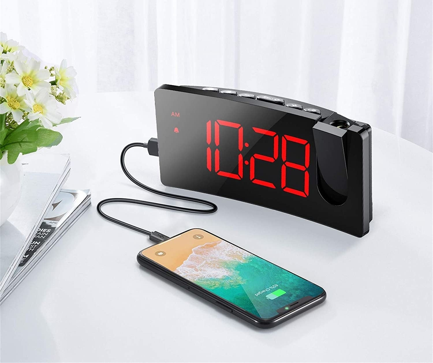 A curved alarm clock with a cell phone plugged in and charging