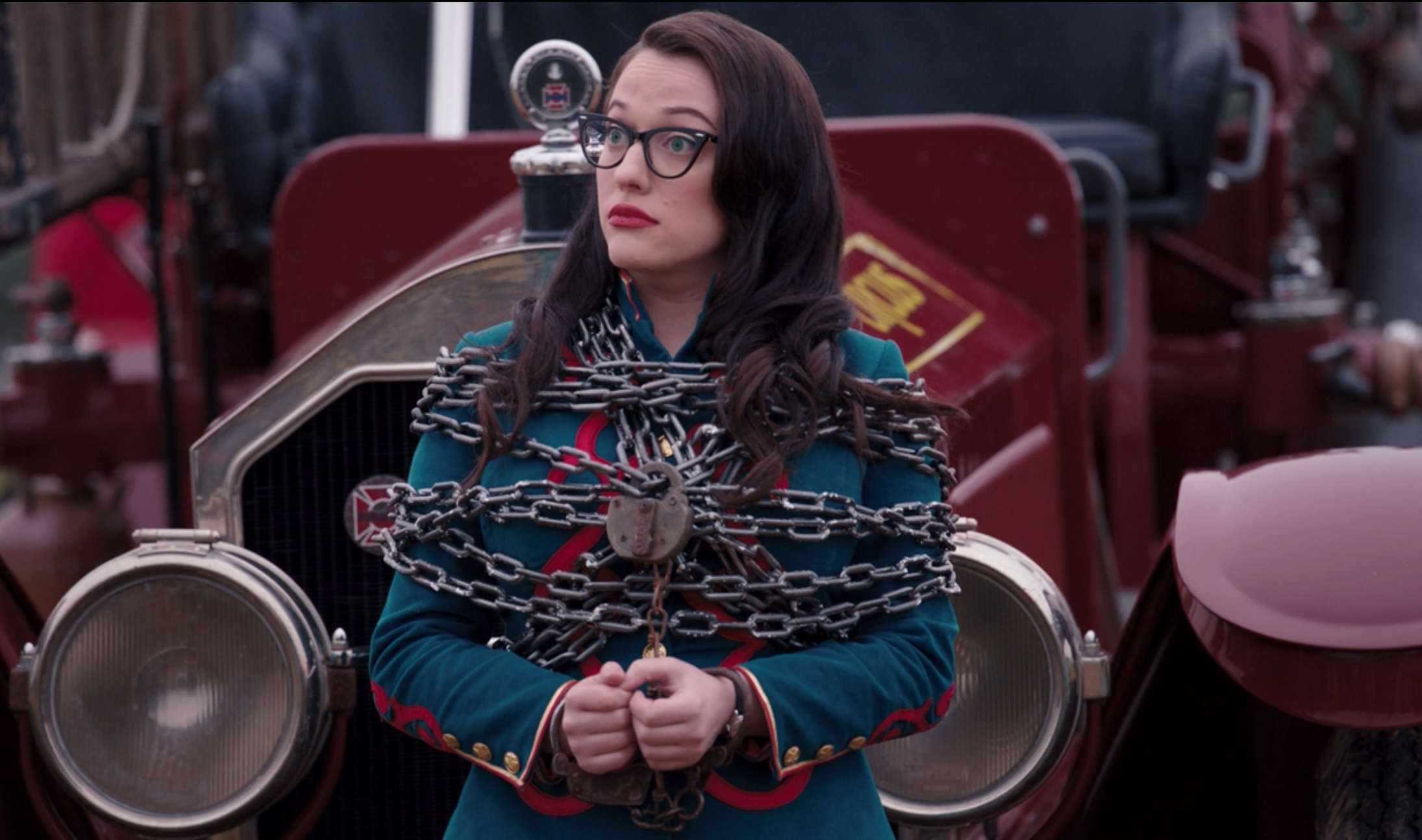 Darcy Lewis has chains across her chest and arms as she stands in front of an old timey car.