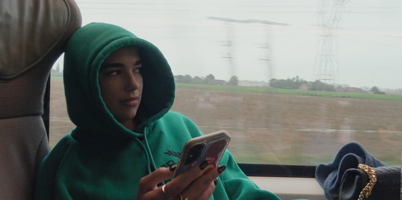 A makeup-less Dua Lipa sits on a tour bus in a hoodie