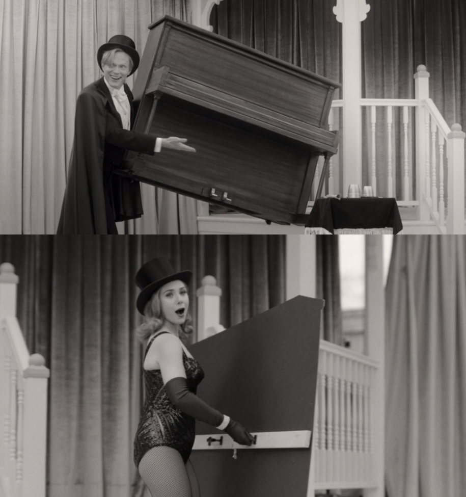 Vision, wearing a suit and top hat, lifts a piano off the ground with one hand and Wanda, wearing a top hat and sparkly body suit, reveals that the piano was a cardboard cut out.