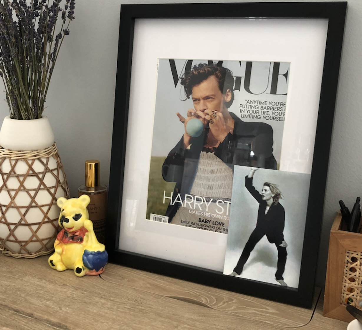 Harry Styles's Vogue cover framed on a wooden desk