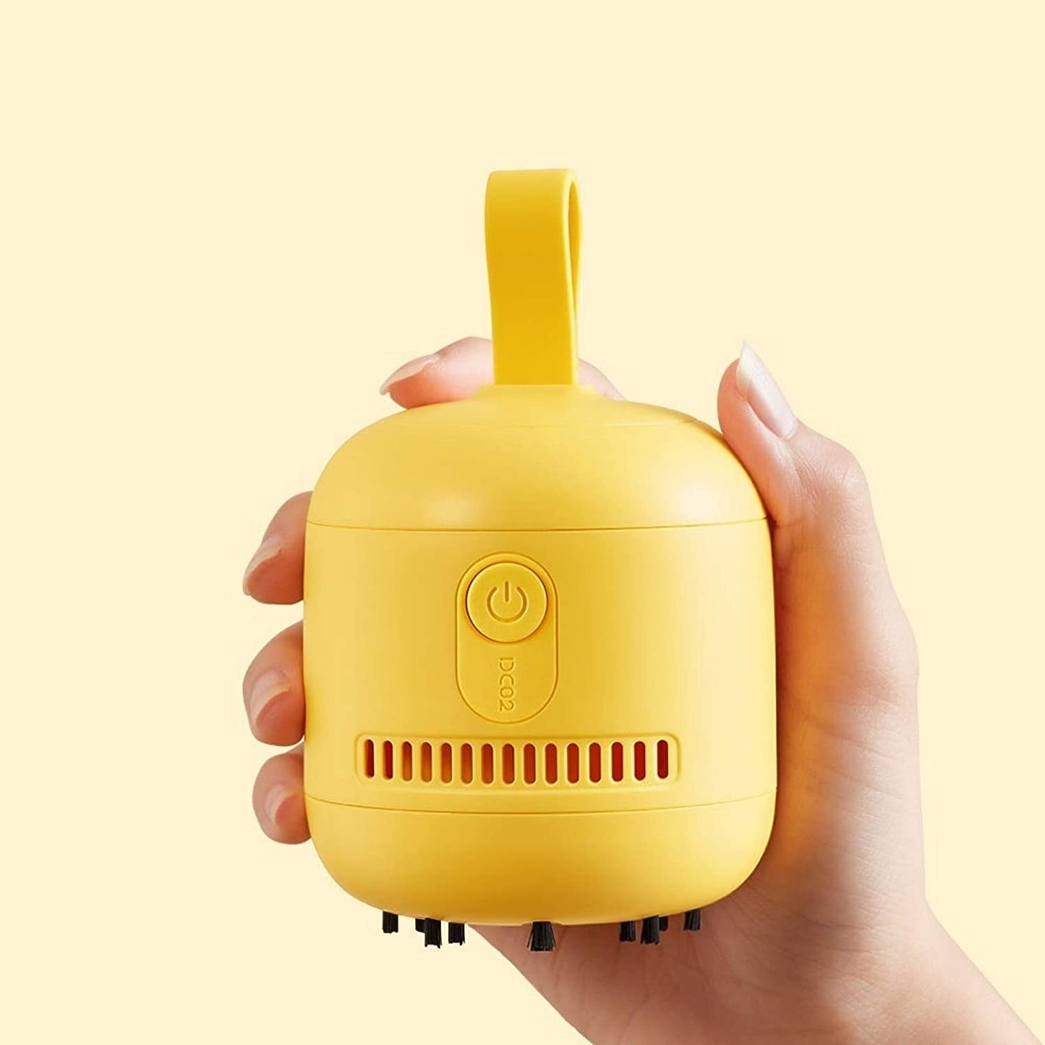 A person holding up a minimalist palm-sized vacuum