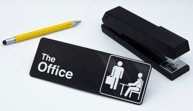 """a black sign that says """"The Office"""" sitting next to a pen and a stapler"""