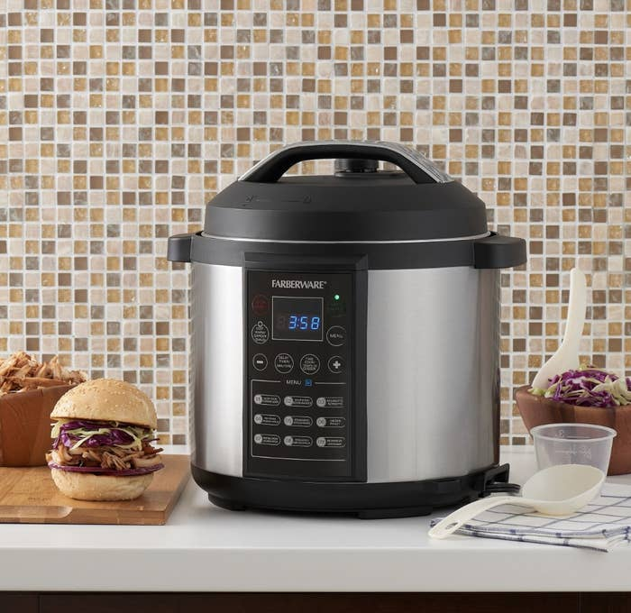 The black and silver cooker is on a countertop and surrounded by pulled pork and coleslaw