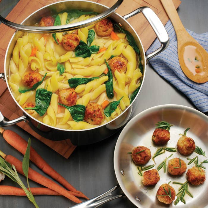 The cookware set cooking a pasta dish and scallops