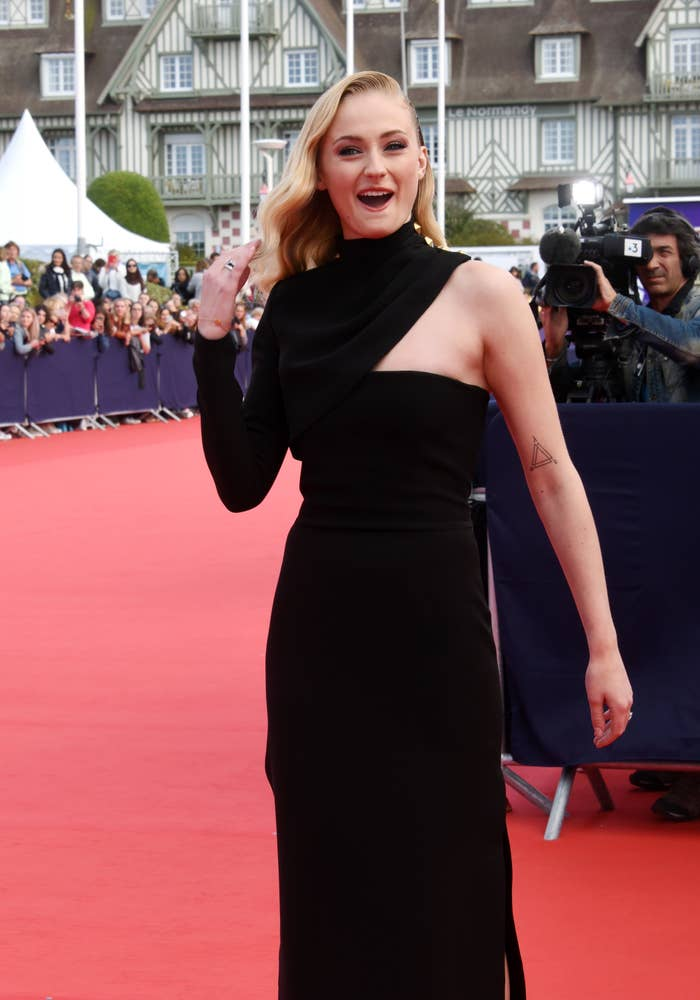 Actress Sophie Turner attends the Heavy Photocall of the 45th Deauville American Film Festival on September 7, 2019 in Deauville, France wearing a black dress, posing with her smiling mouth agape