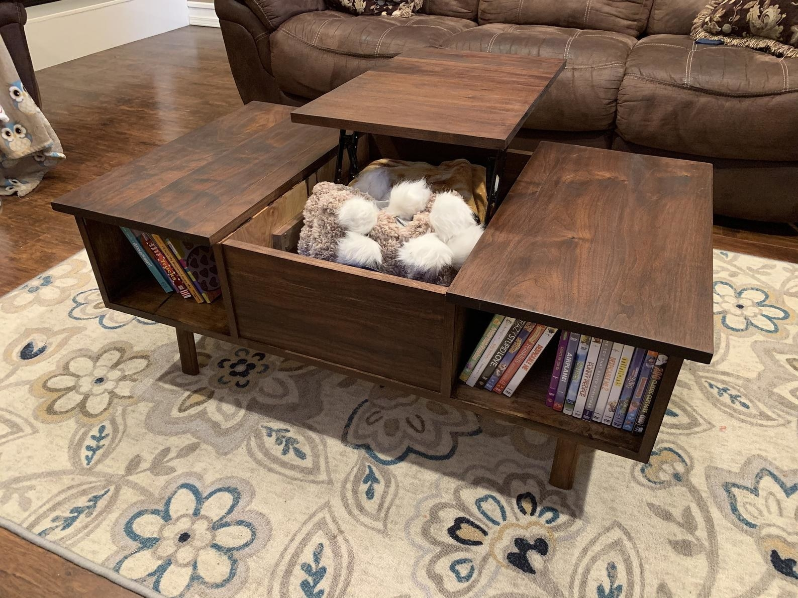 in a living room, the lift-top desk is open to reveal childrens' toys