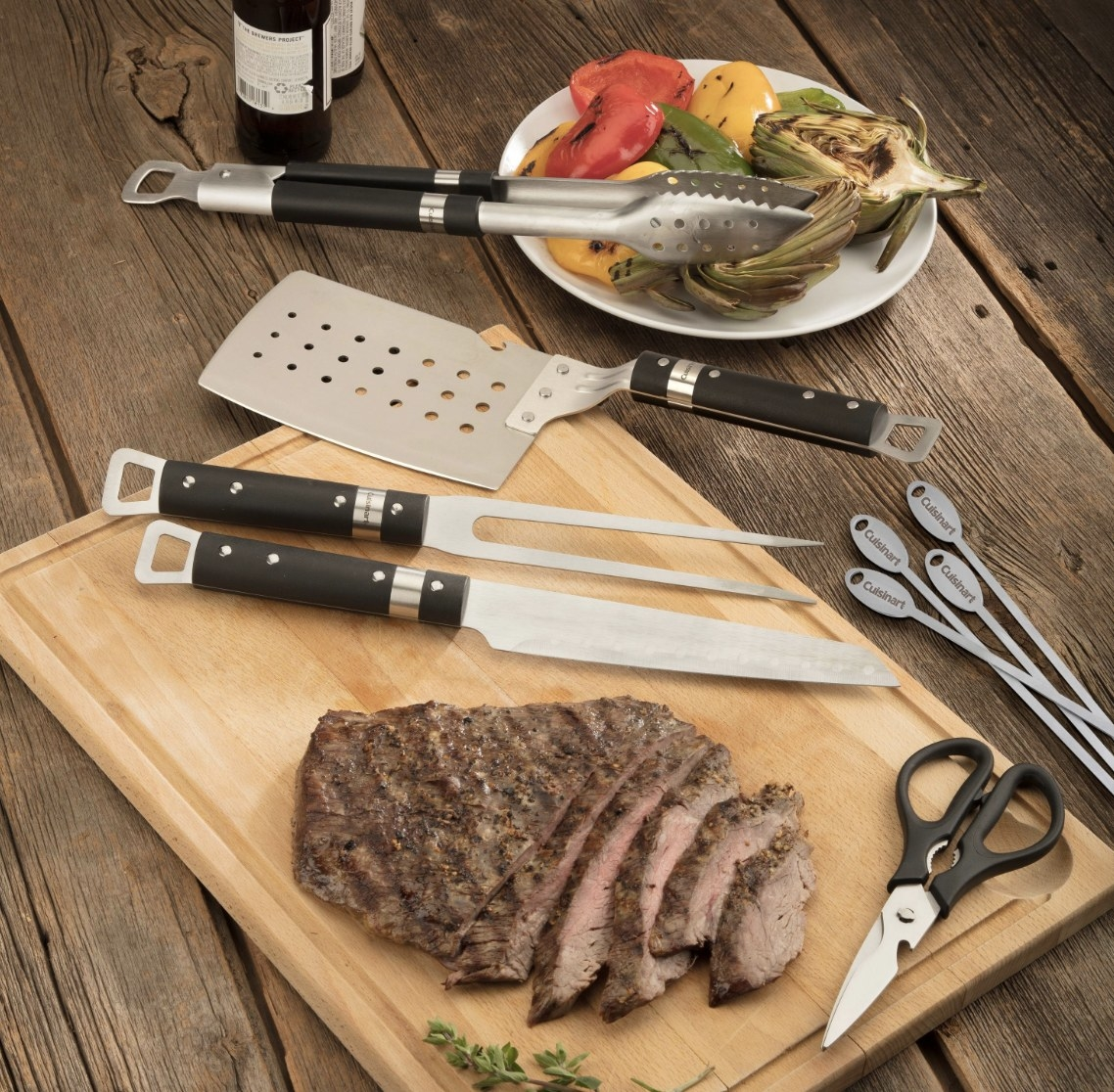 There is a bamboo board with a sliced piece of meat and assorted metal and black tools