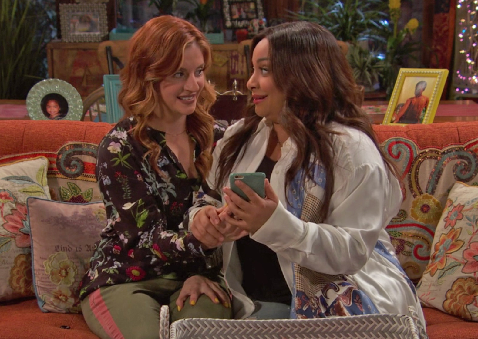 Chelsea and Raven smiling at each other and holding a cellphone with their hands