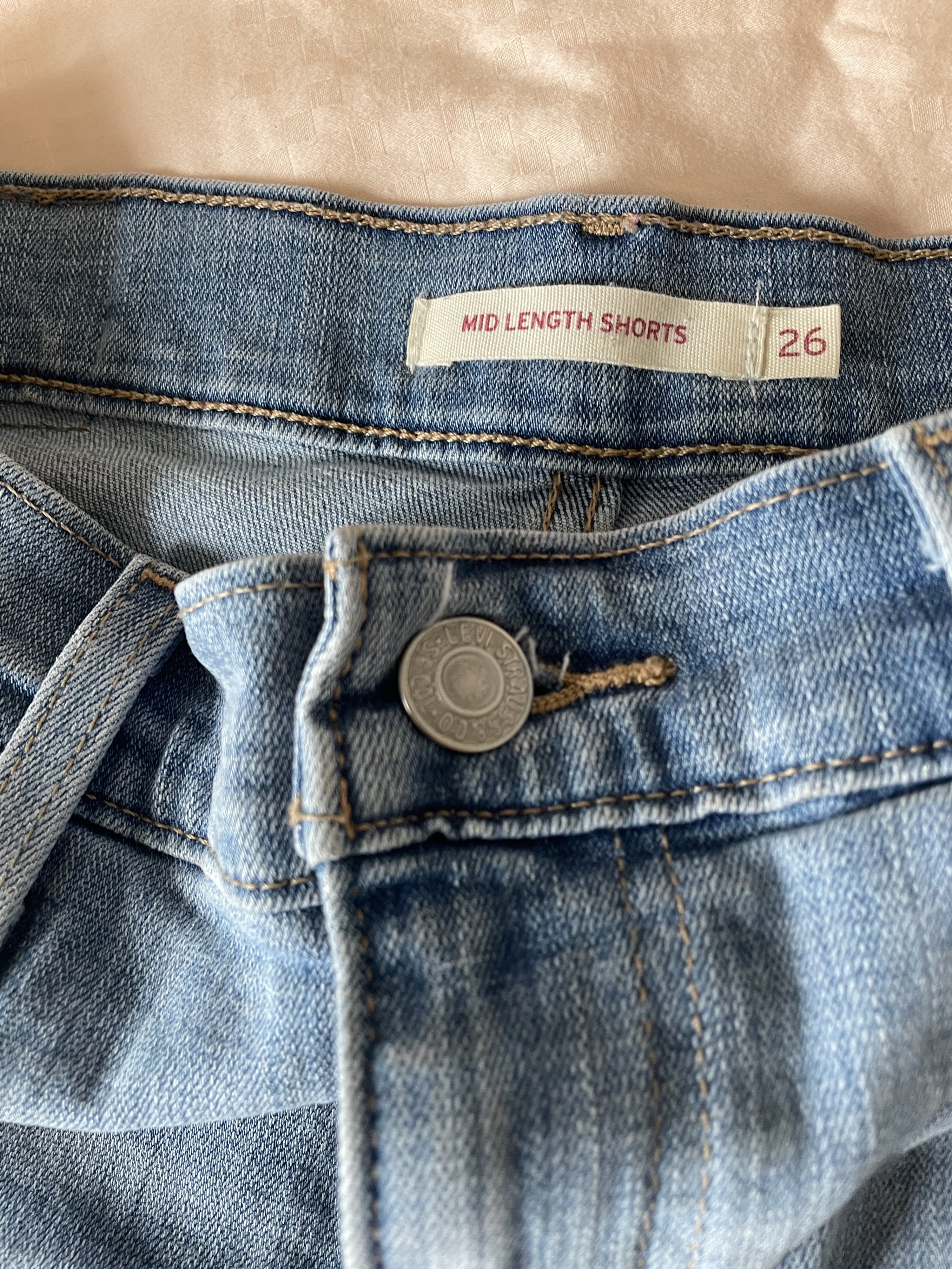 """writer's photo closeup of seams and tag on the back of shorts. it reads """"Mid Length Shorts 26"""""""