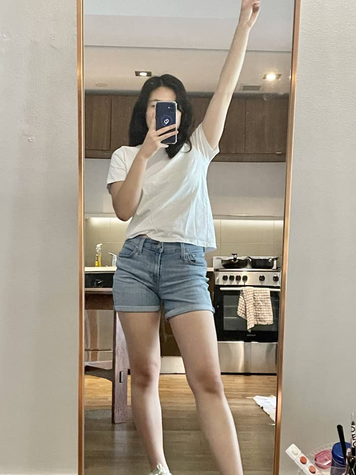 Writer wearing shorts in front of full length mirror
