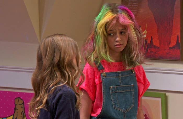 Sydney furrows her brows, concerned, as she rocks a rianbow hairdo