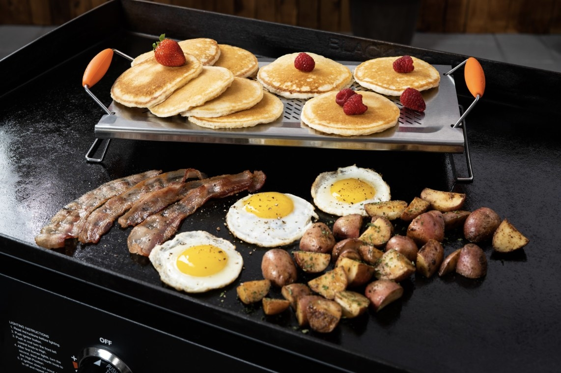 The stainless steel warming rack is holding pancakes and strawberries and is surrounded by breakfast food
