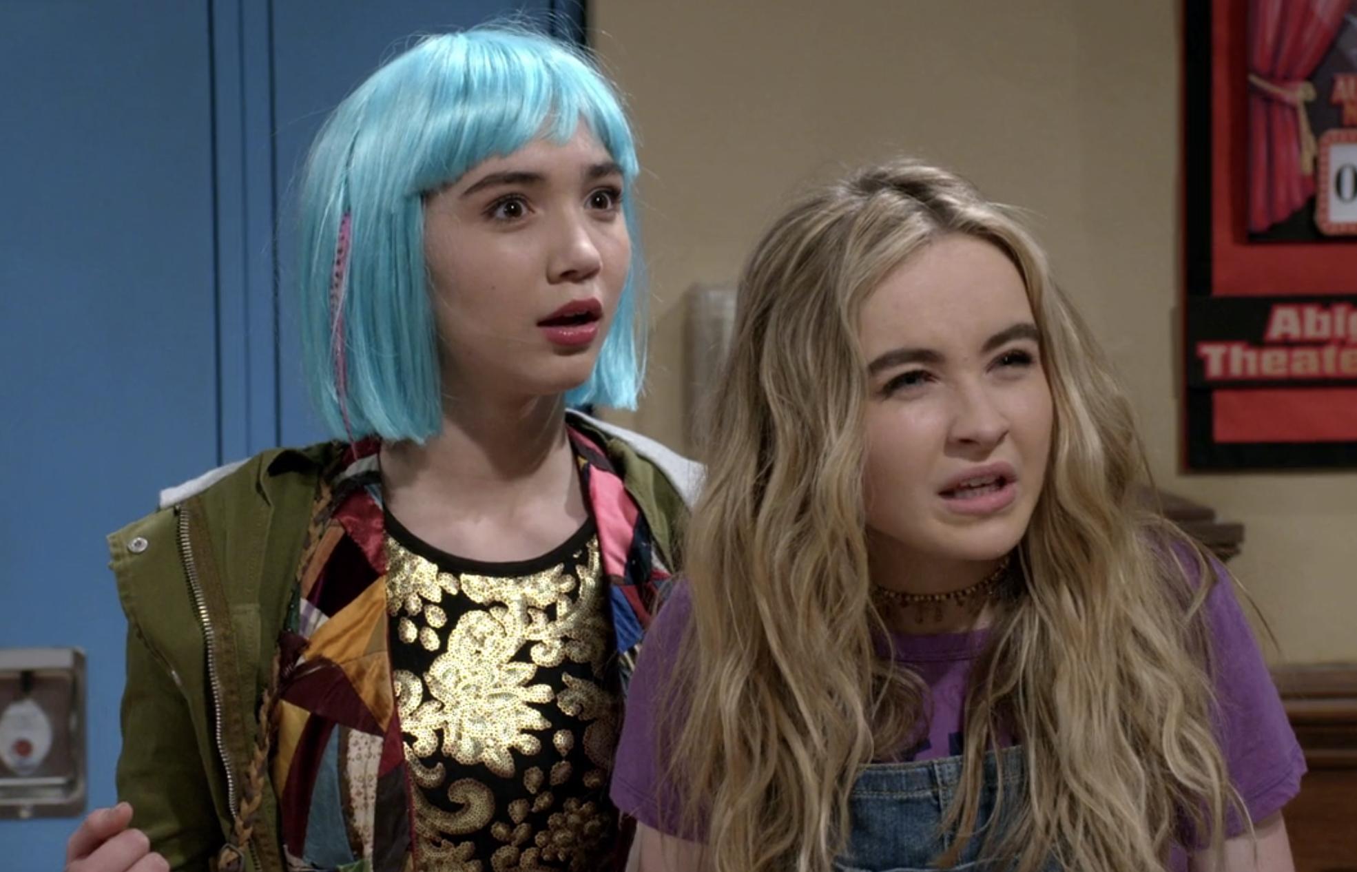 Riley, wearing a short bob wig, and Maya squint in confusion