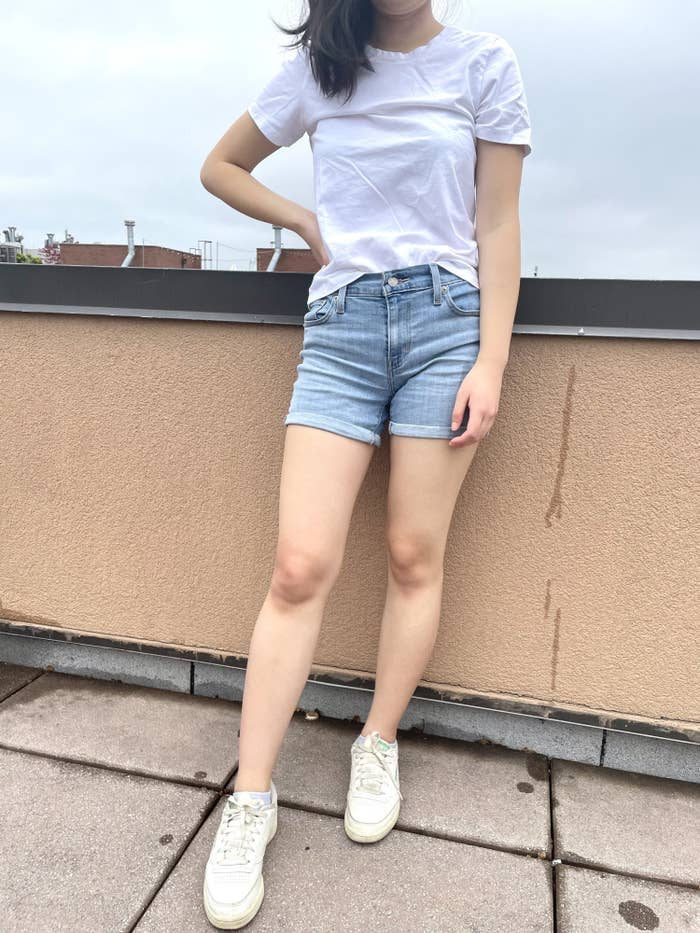 writer photo wearing the shorts and a white t-shirt standing on a roof