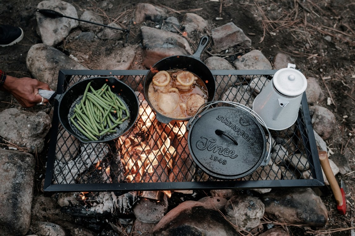 The cast iron set is above an outdoor fire and is roasting various foods