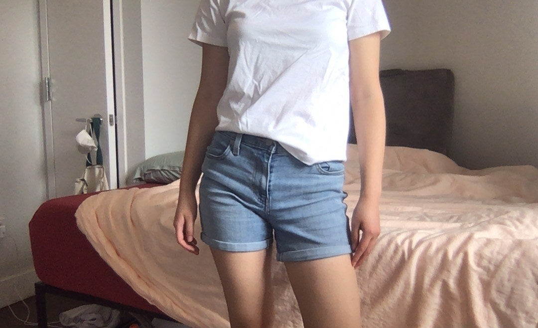 writer photo wearing the shorts standing in bedroom