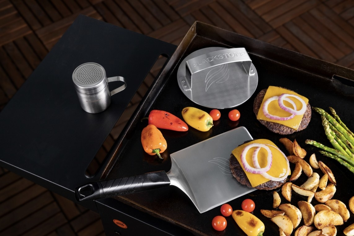 The three stainless steel tools are on a grill next to hamburgers and various veggies