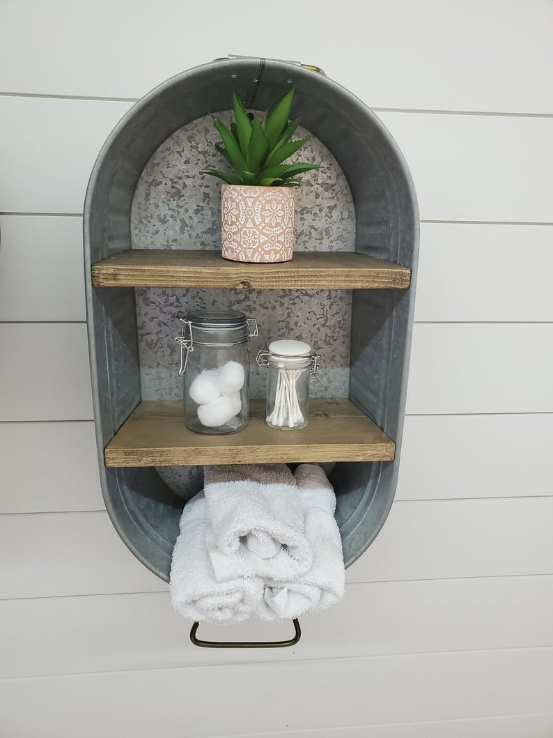 the galvanized wash tub with wooden shelves mounted on a wall with toiletries on each shelf