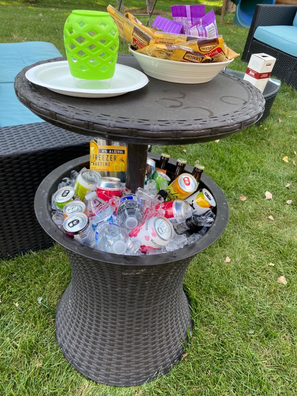 The hgih top table extending out of the cooler base, with food on the table and drinks and ice in the cooler base