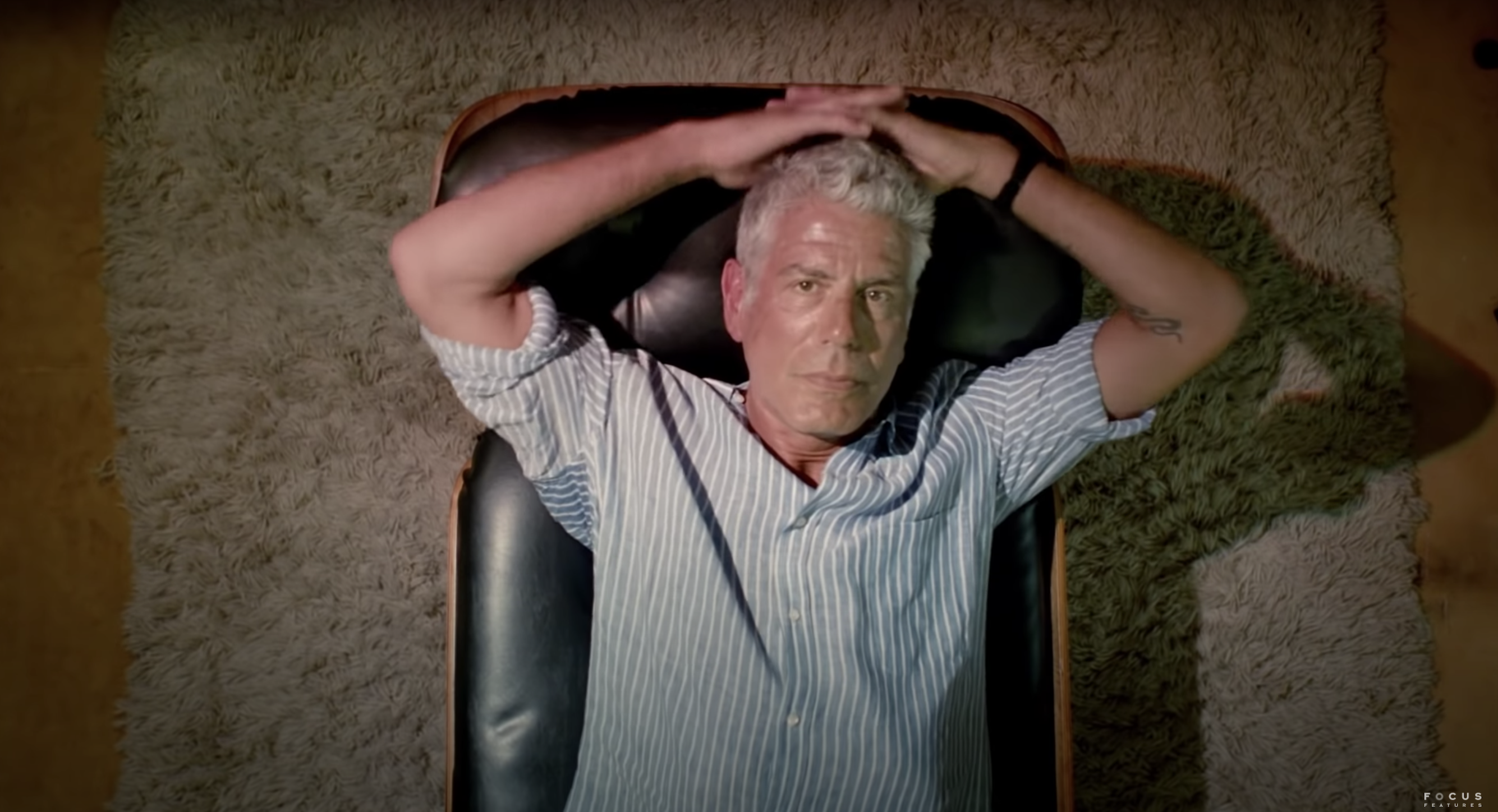 An arial shot of Anthony Bourdain shows the chef laying down on a black leather seat, hands behind his head