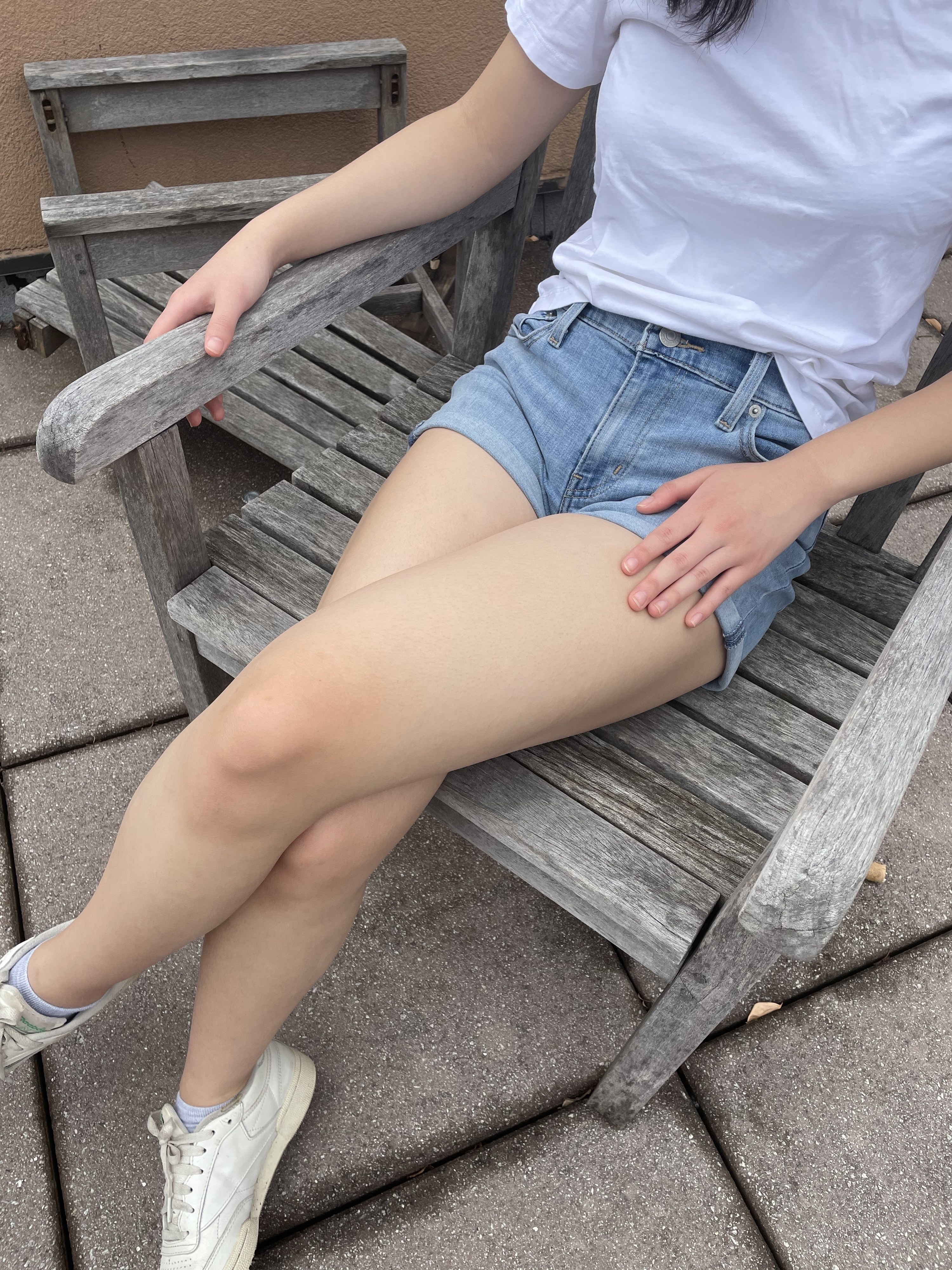 writer photo wearing shorts sitting on a chair outdoors
