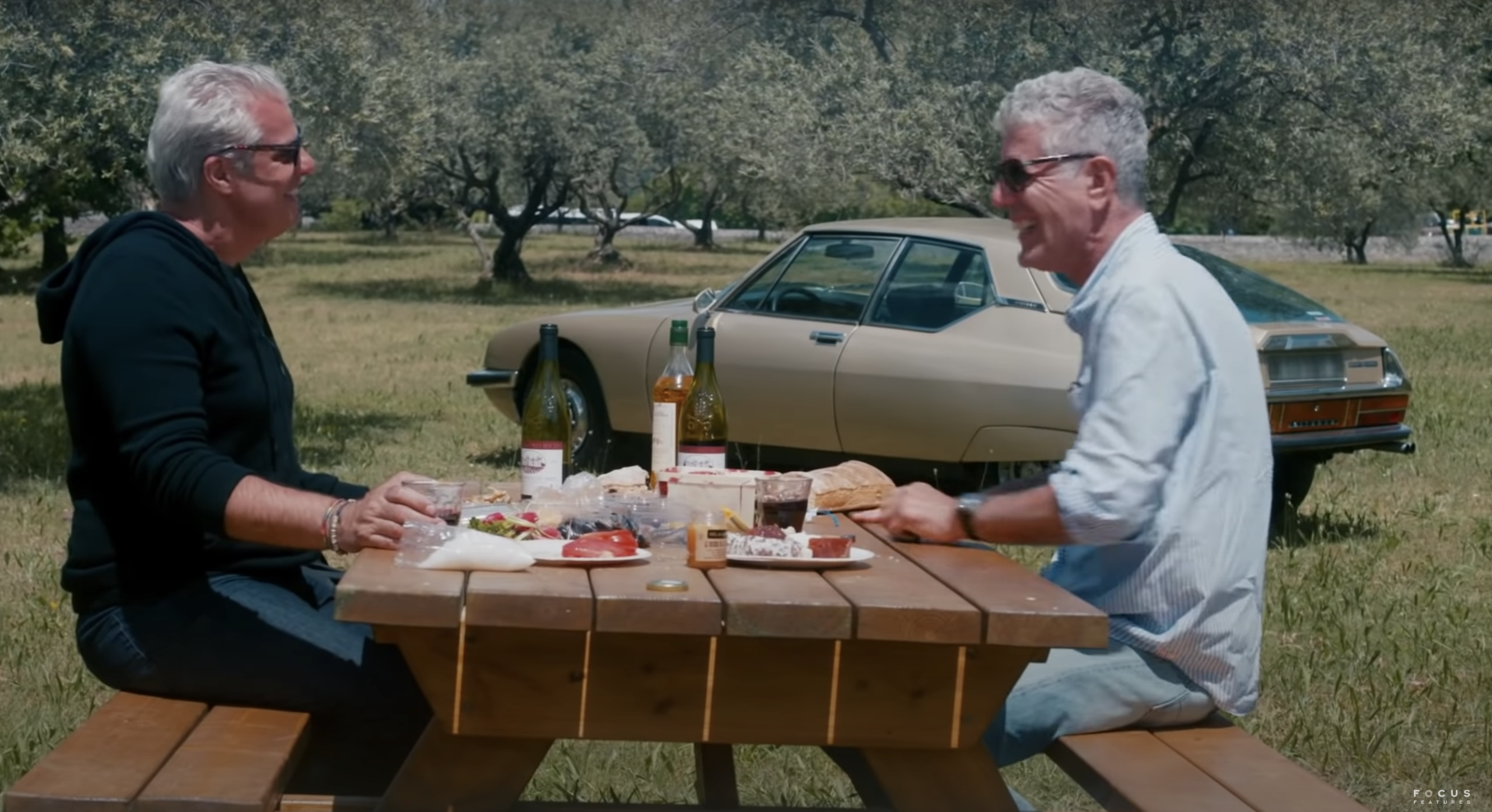 French chef Eric Ripert and Anthony Bourdain sit outside, laughing over a picnic of wine, bread, and cheese