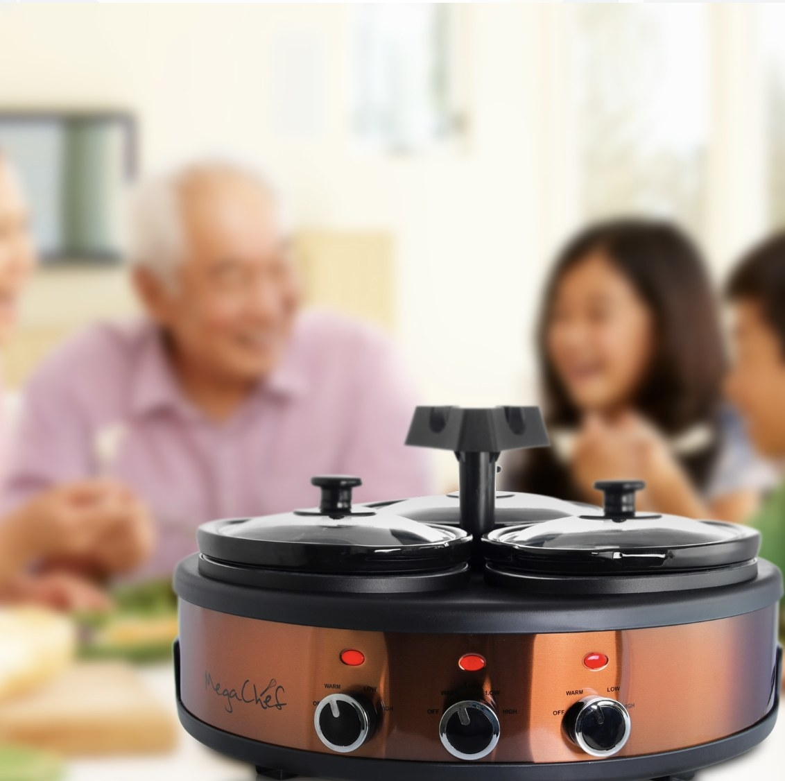 The slow cooker is a copper and black color and there is a group of young and old people laughing in the background