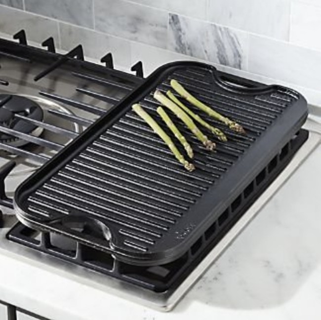 The black cast iron griddle has asparagus cooking on top