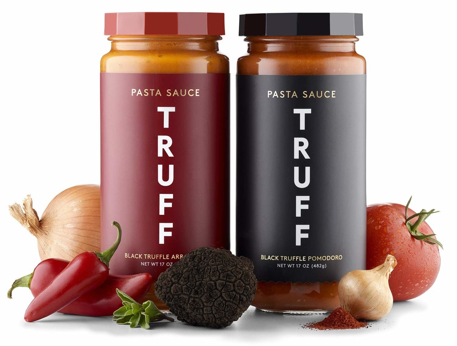 The jars of the Truff Pomodoro and Arrabbiata sauces next to onions, chilis, garlic, tomatoes, and truffles