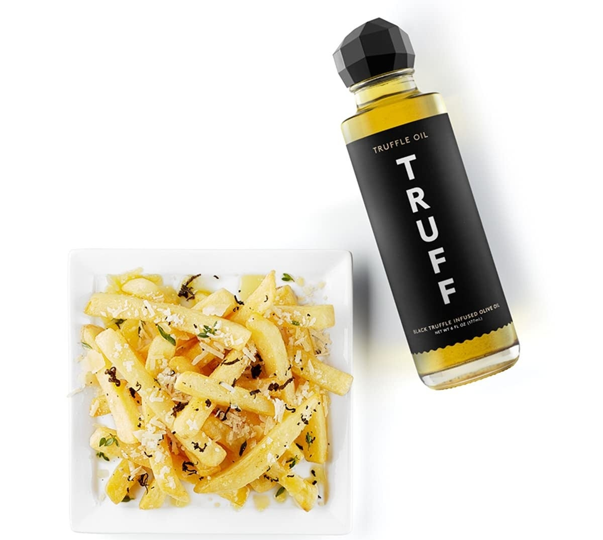 A bottle of the truffle oil sitting next to a plate of seasoned fries