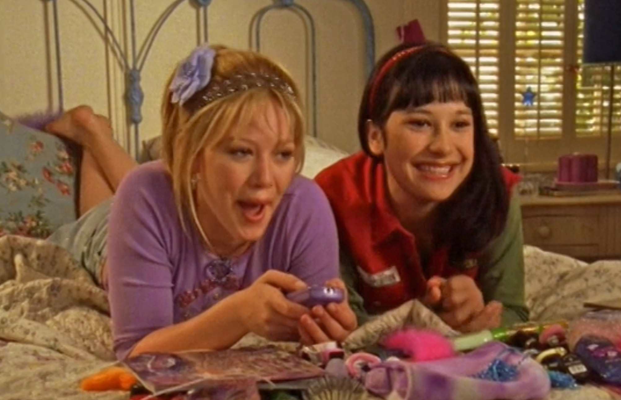 Lizzie and Miranda sit lie on the bed with magazines and a cellphone in front of them