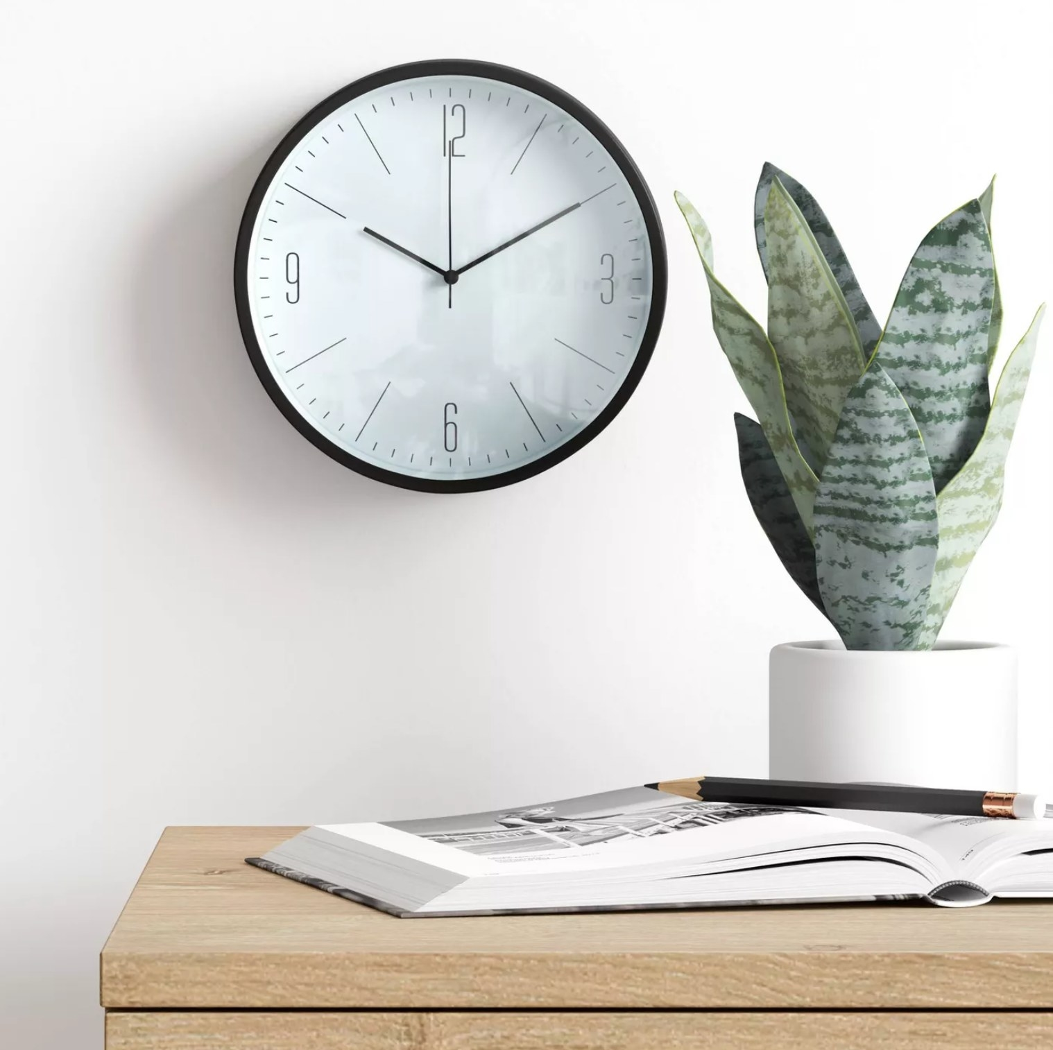 the clock hanging on the wall above a plant and a book