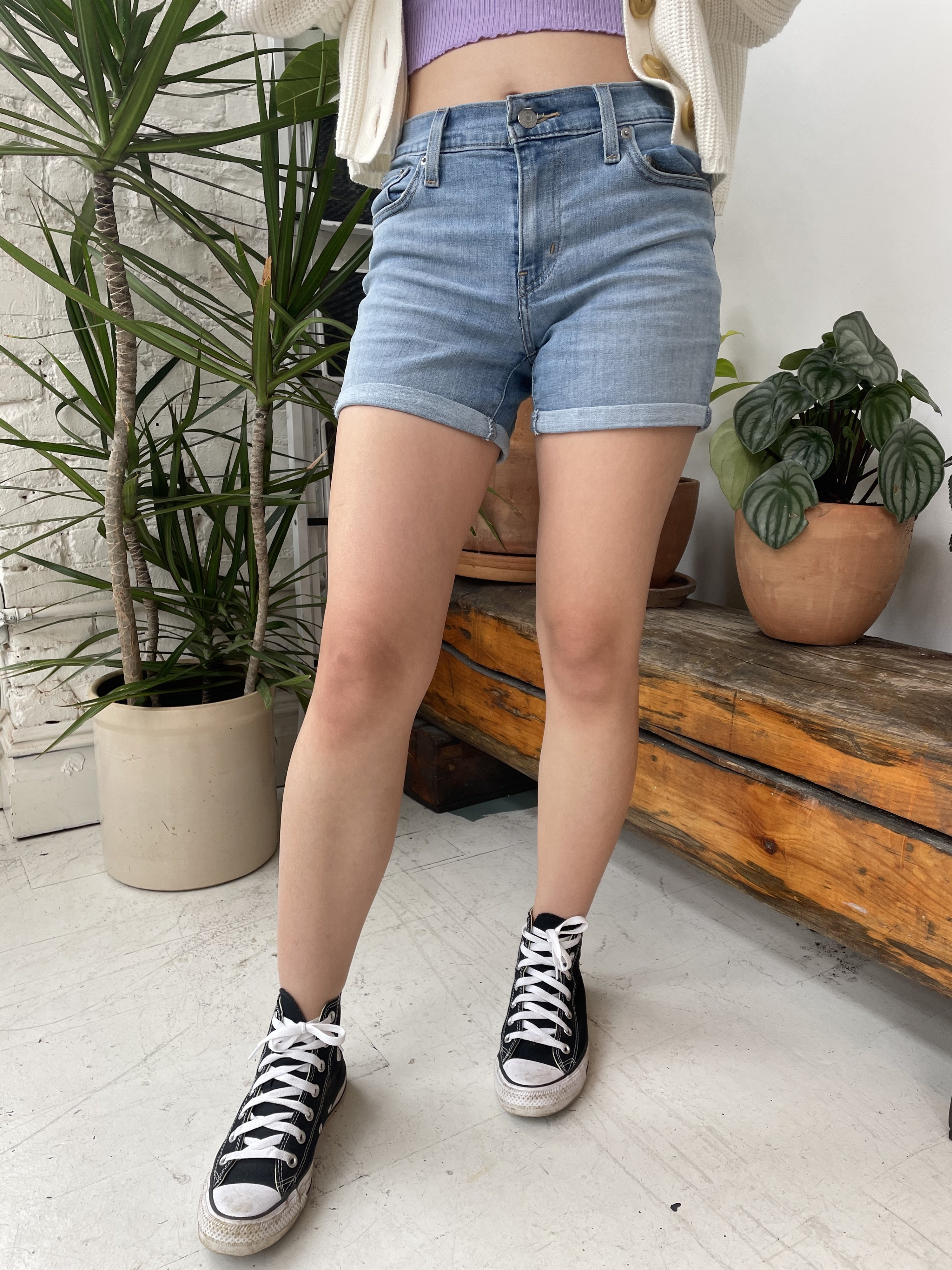 writer wearing the shorts with hi-top black converse, plants in the background