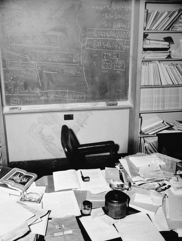 Equations written on a chalkboard that overlook a messy desk scattered with papers