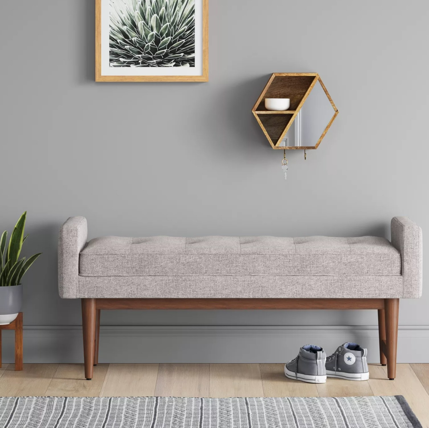 the gray bench with shoes underneath and wall decor above